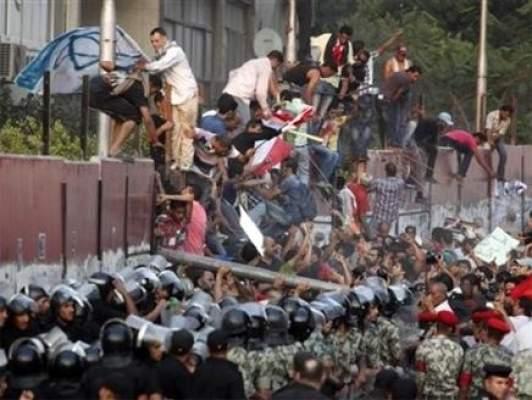 Photo of مصريون غاضبون من فيلم مسيء للرسول يتسلقون أسوار السفارة الامريكية بالقاهرة ويمزقون العلم الامريكي